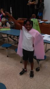 A student at Blue Lick Elem. wearing her cape, doing her Superhero pose