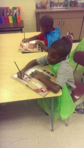 Two students at Cane Run Elem. working in their activity books while wearing their Superhero capes.